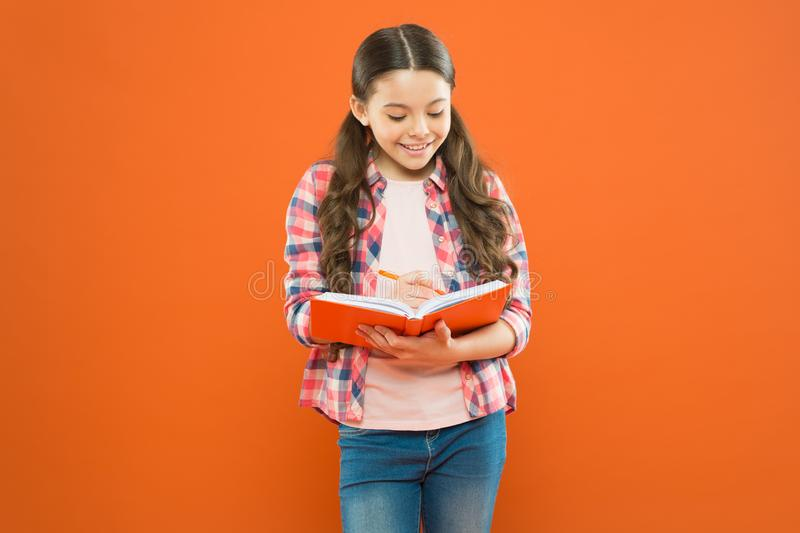 Girl cute write down idea notes. Notes to remember. Write essay or notes. Exercising writing workbook. Making notes. Child doing homework writing in workbook stock photography
