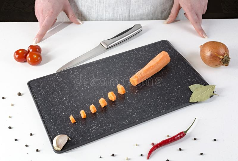 Girl cuts carrots into small slices on a black cutting board stock image