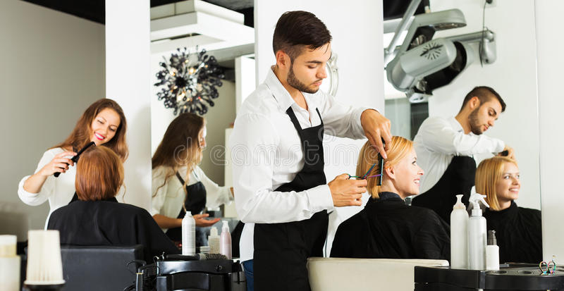 Girl cuts hair at the hair salon. Hairdresser cuts young girl's hair in the beauty salon royalty free stock photo