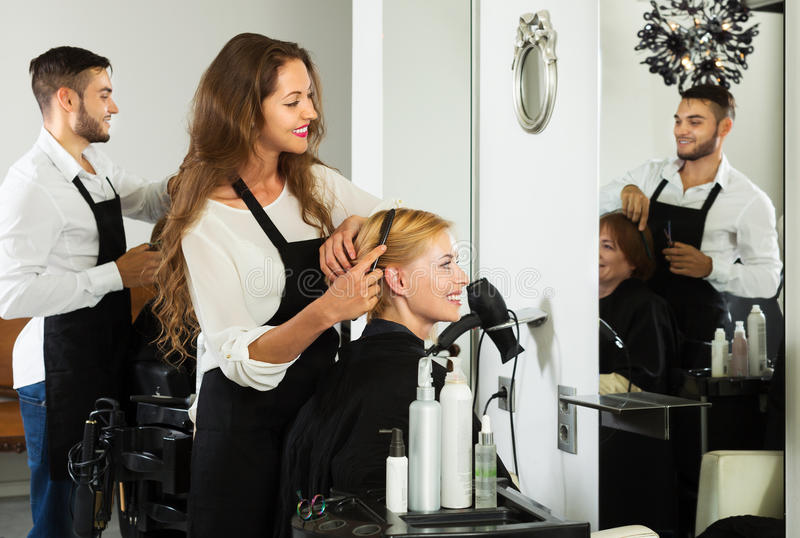 Girl cuts hair at the hair salon. Young women cuts hair at the hair salon stock photography