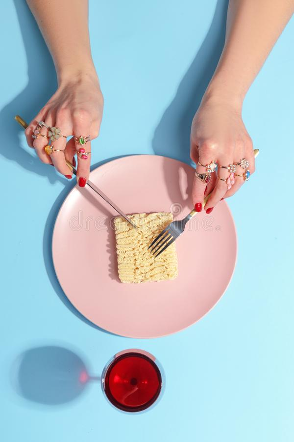 The girl cuts with a knife and fork noodles on a pink plate. Minimalistic concept. Top view stock image