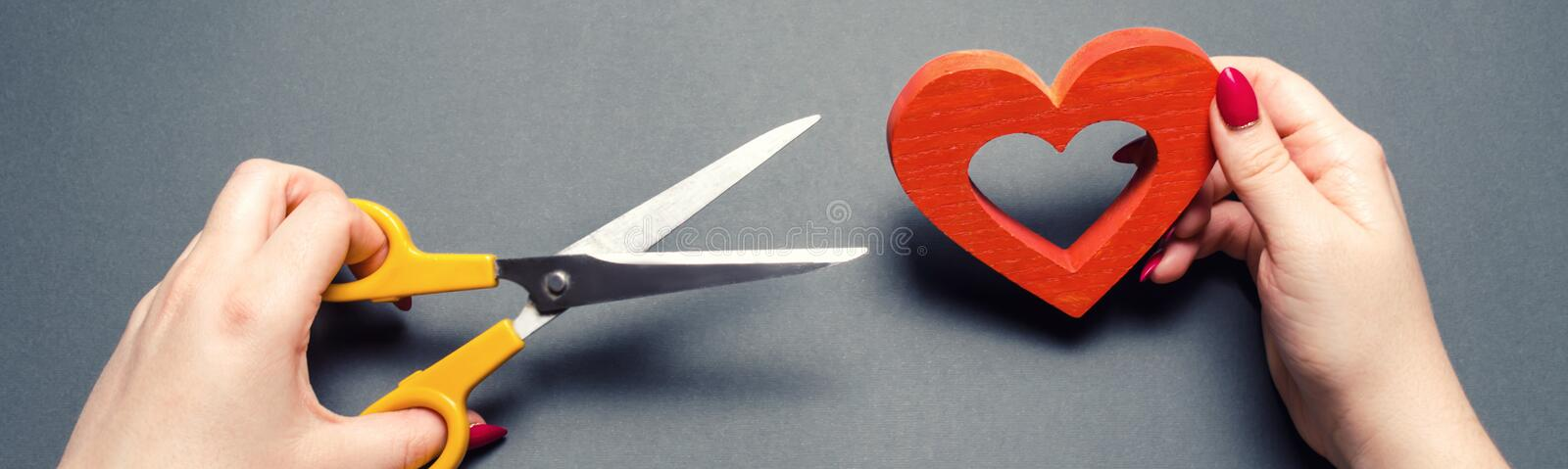 Girl cuts the red heart with scissors. The concept of breaking relations, quarrels and divorce. Betrayal of the othere. Loss of. Feelings for your loved one royalty free stock photography