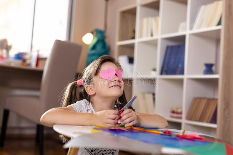 Girl cutting colorful paper. Little girl playing in a playroom, cutting colorful paper, making decorations for an art project for school and having fun royalty free stock images