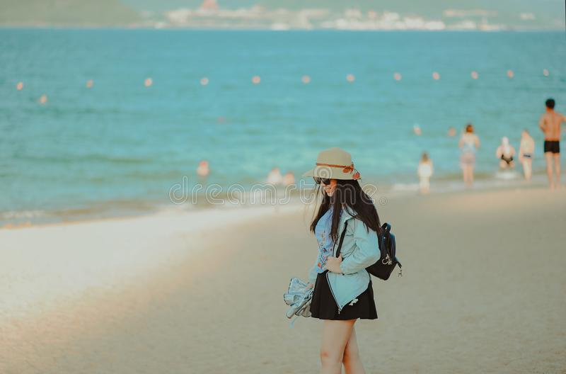 Girl in Cyan Jacket Walking on Beach royalty free stock photo