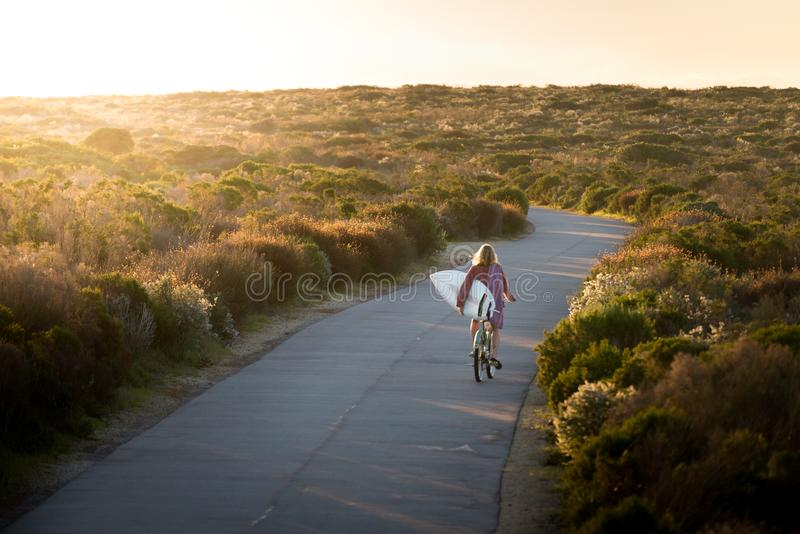Beautiful blonde surfer girl on her way to the beach on her bicycle with her surfboard. royalty free stock photos