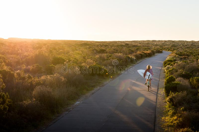 Beautiful blonde surfer girl on her way to the beach on her bicycle with her surfboard. royalty free stock photography