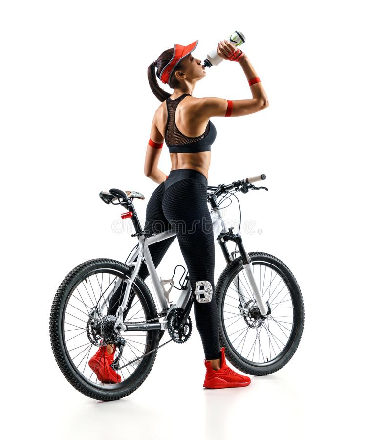 Girl cyclist with bicycle drinking a water on white background stock image