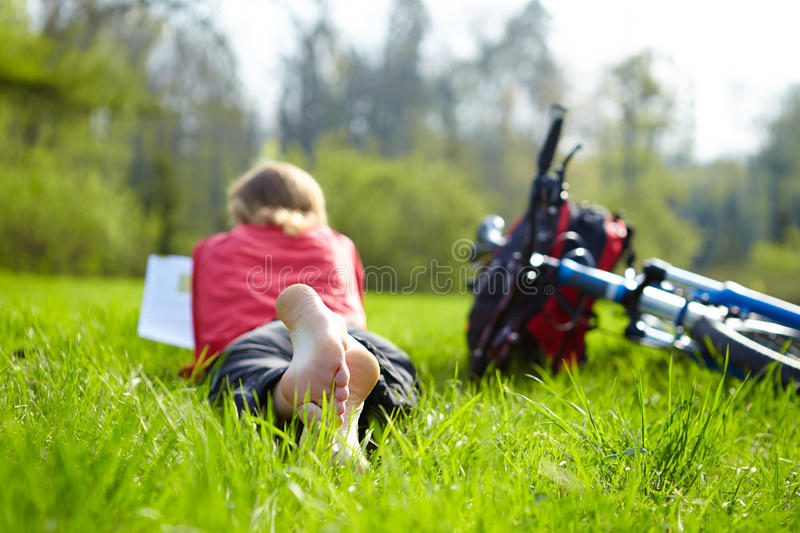 Girl cyclist on a halt reads on green grass outdoors in spring park. Enjoying relaxation stock photography
