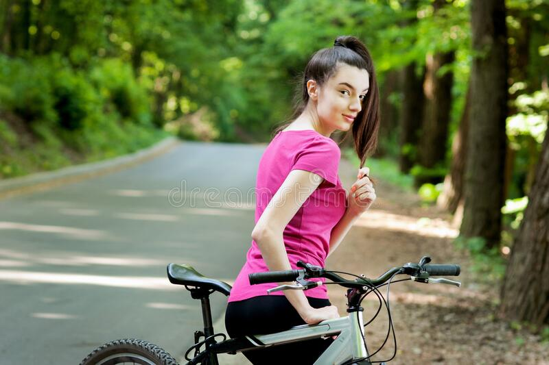 Girl cyclist in pink standing with bike on asphalt road in the forest. Female cyclist in pink standing with bike on asphalt road in the forest stock images