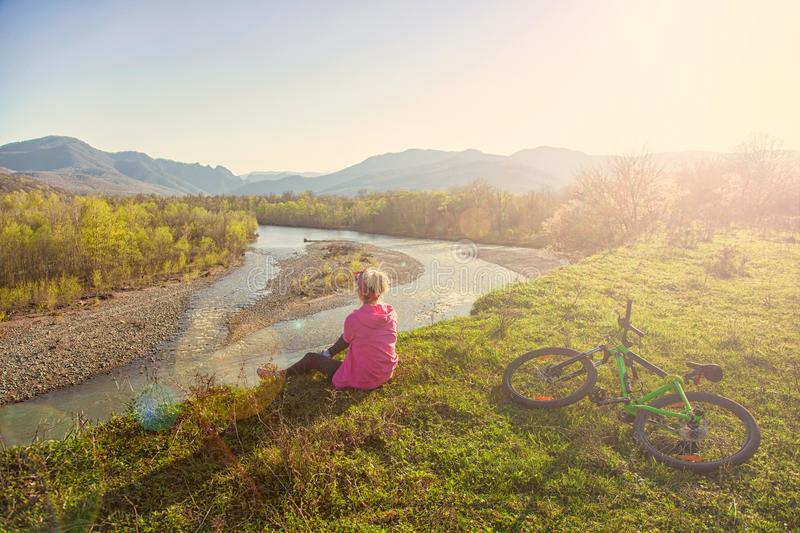 Girl cyclist sits on a mountain and looks at the river at sunset royalty free stock images