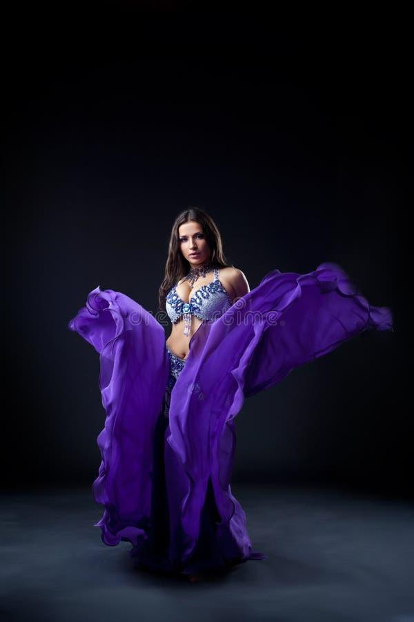 Girl dance in dark - oriental flying purple cloth royalty free stock images