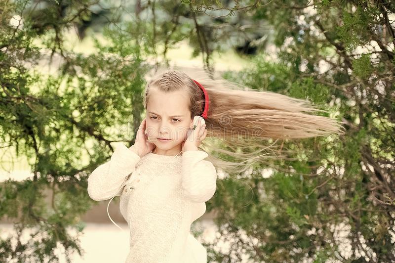 Girl dance to music in summer park. Small child enjoy music in headphones outdoor. Kid dancer with long flying hair. Melody sound and mp3. Summer fun and joy royalty free stock photo