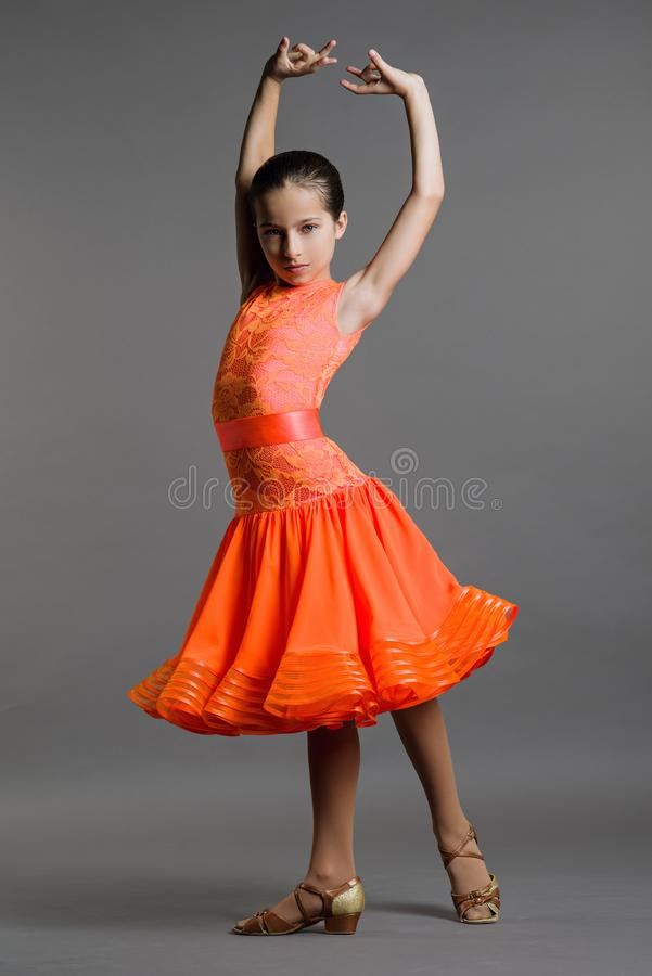 Girl dancer ballroom dancing poses on a gray background. stock photo