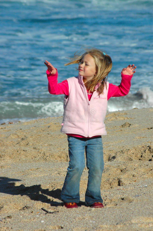 Girl dancing on beach. A little Caucasian happy girl child enjoying wind and sun by dancing in the sand on the beach royalty free stock images