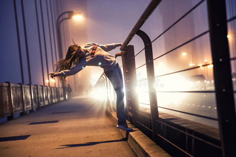 Girl dancing on bridge royalty free stock photography