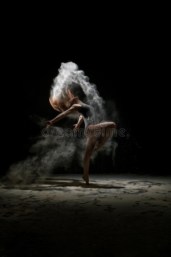 Girl dancing in a cloud of white dust studio portrait stock photography