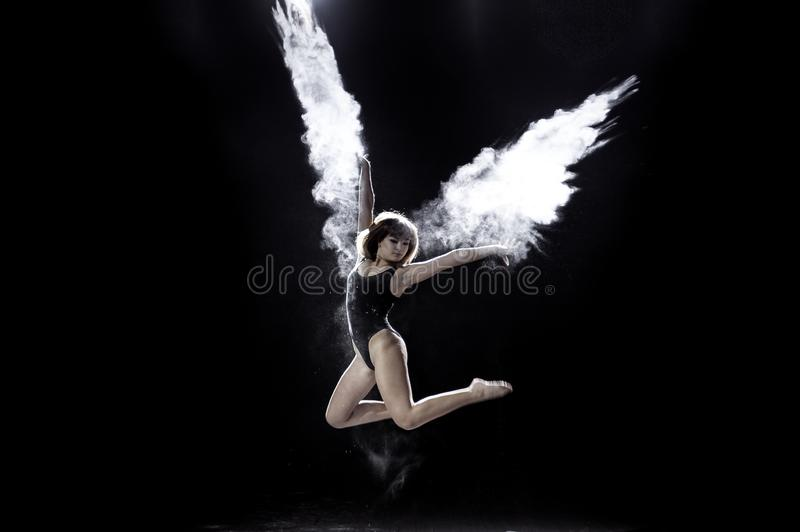 Girl dancing with a flour on black background. stock photos