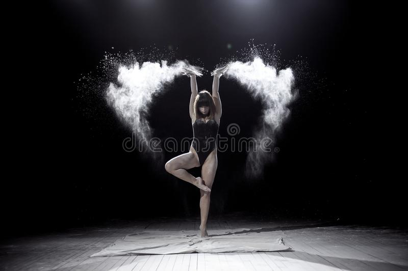 Girl dancing with a flour on black background. stock photography