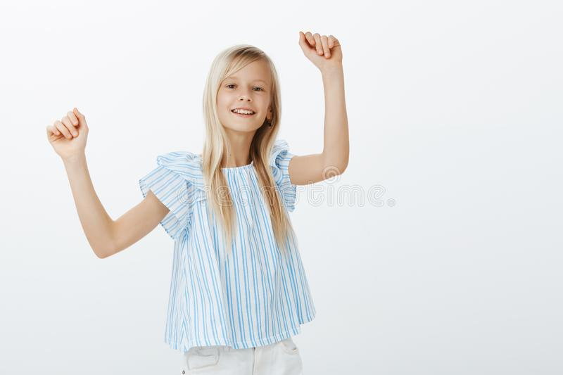 Girl dancing on friends party, having fun. Indoor portrait of positive cheerful bright female child with fair hair royalty free stock images