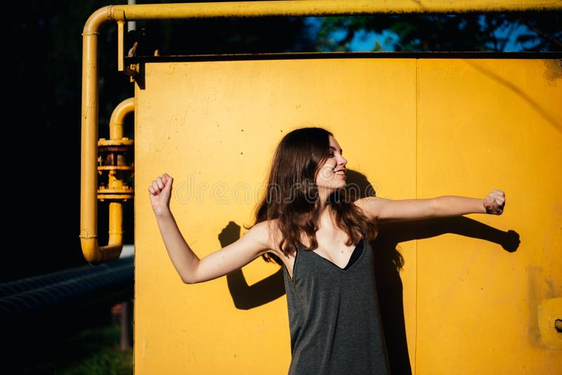 Girl dancing in front of a yellow wall stock image