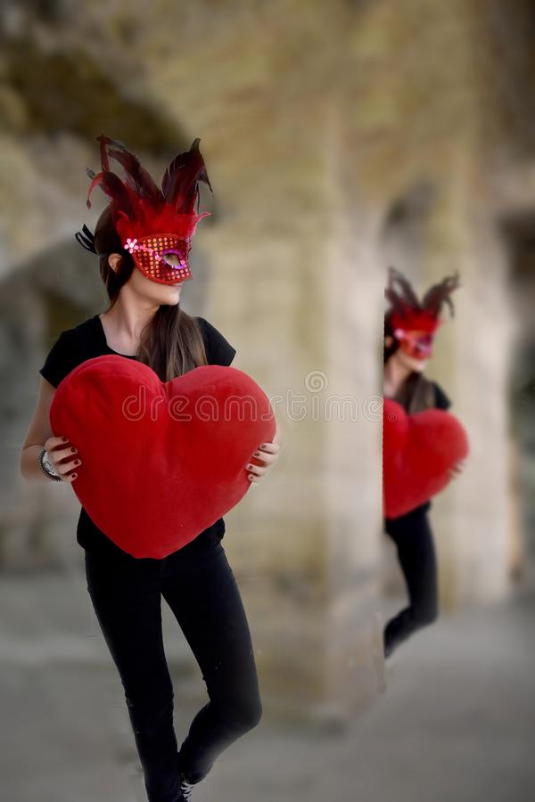 Girl in carnival dancing with big red heart royalty free stock images