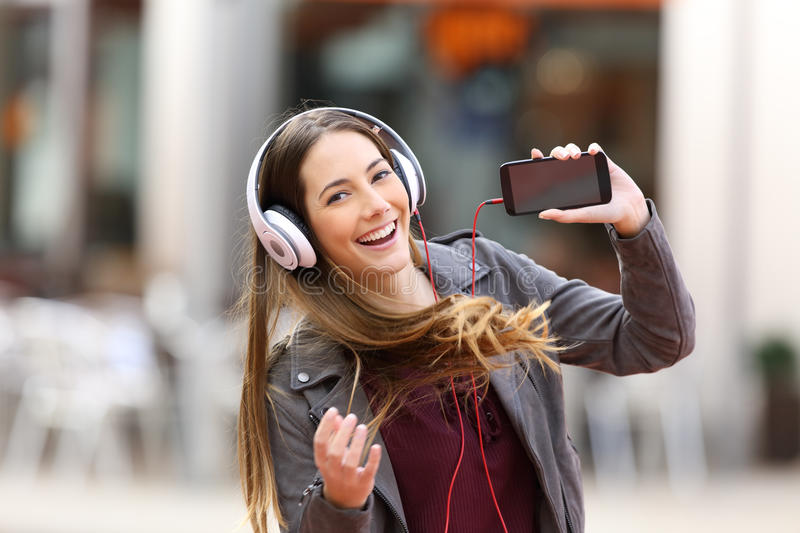 Girl dancing and listening music looking at you. Fashion girl dancing and listening music showing a blank screen of a smart phone and looking at you in the royalty free stock photos