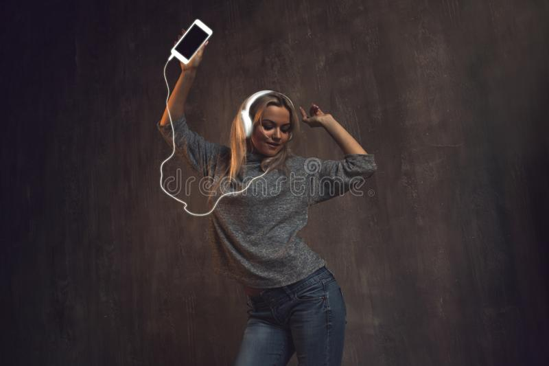Girl dancing and listening to music in a mobile application. royalty free stock images