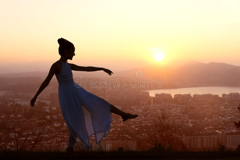 Girl dancing on top of mountain overlooking the city stock images
