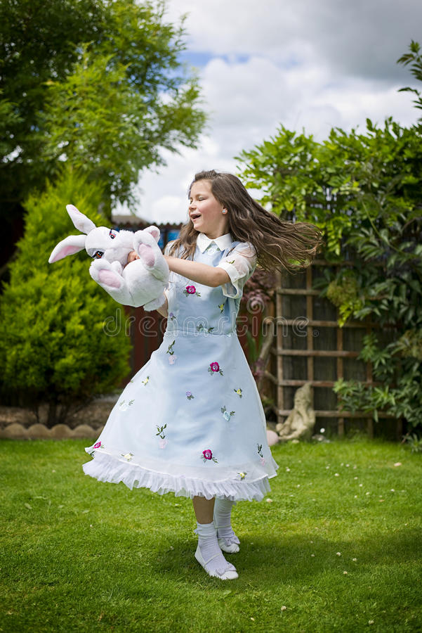 Girl dancing with toy. Young girl playing, dancing with toy rabbit royalty free stock photography