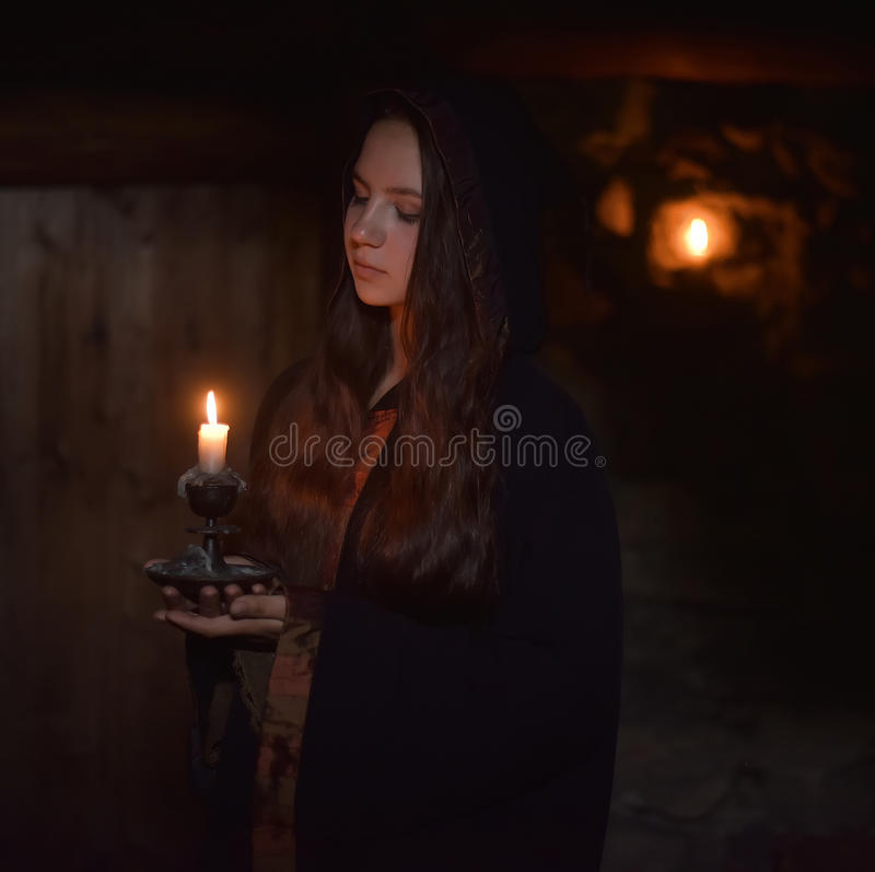 Girl in a dark cloak. With a candle stock image