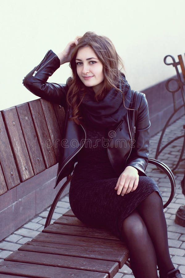 Girl in a dark clothes sitting on a striped wooden bench royalty free stock images