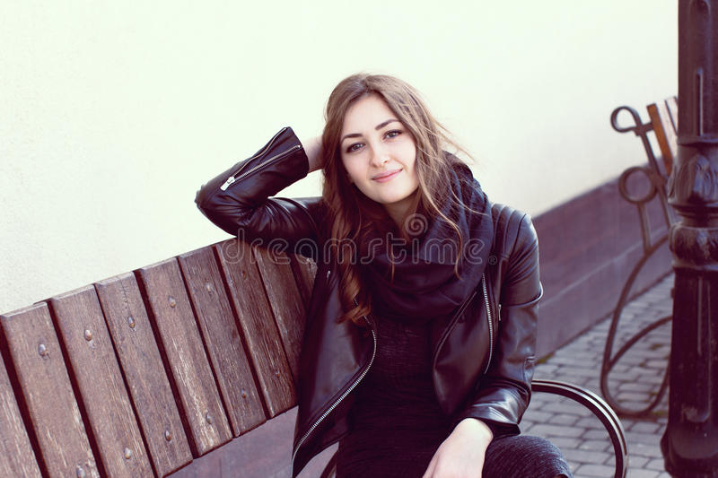 Girl in a dark clothes sitting on a striped wooden bench royalty free stock image