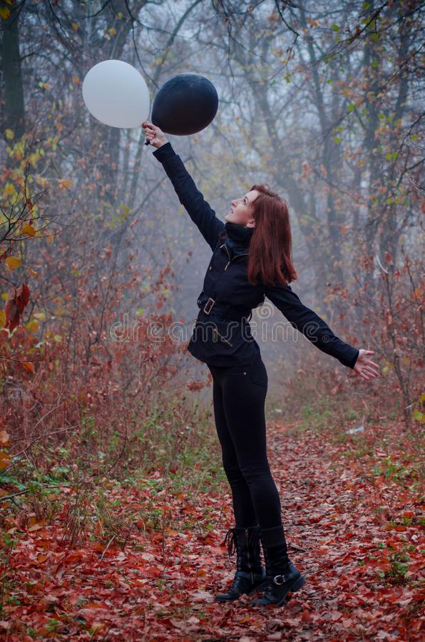Girl in dark clothing in autumn fog forest, with flying two balloons, black and white. Concept of choice, good and evil stock photos
