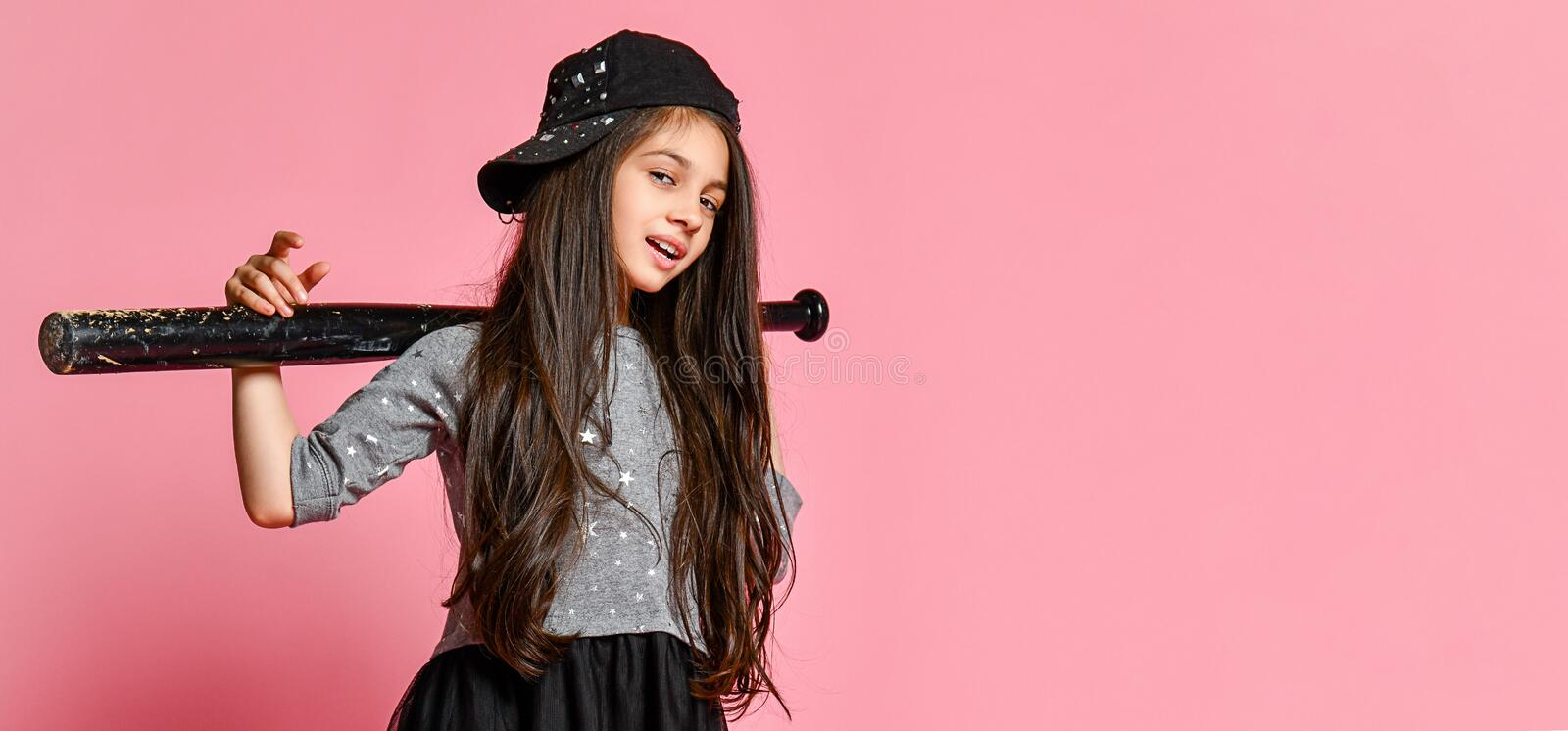 Young bright american girl with baseball bat. Girl in a dark dress, with a mesh skirt and sneakers, wearing a cap, holding a baseball bat on a pink royalty free stock photos