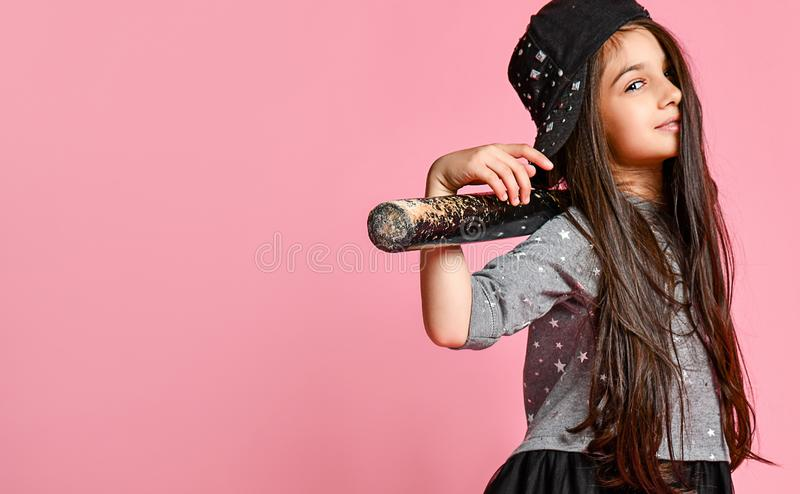 Young bright american girl with baseball bat. Girl in a dark dress, with a mesh skirt and sneakers, wearing a cap, holding a baseball bat on a pink stock photos