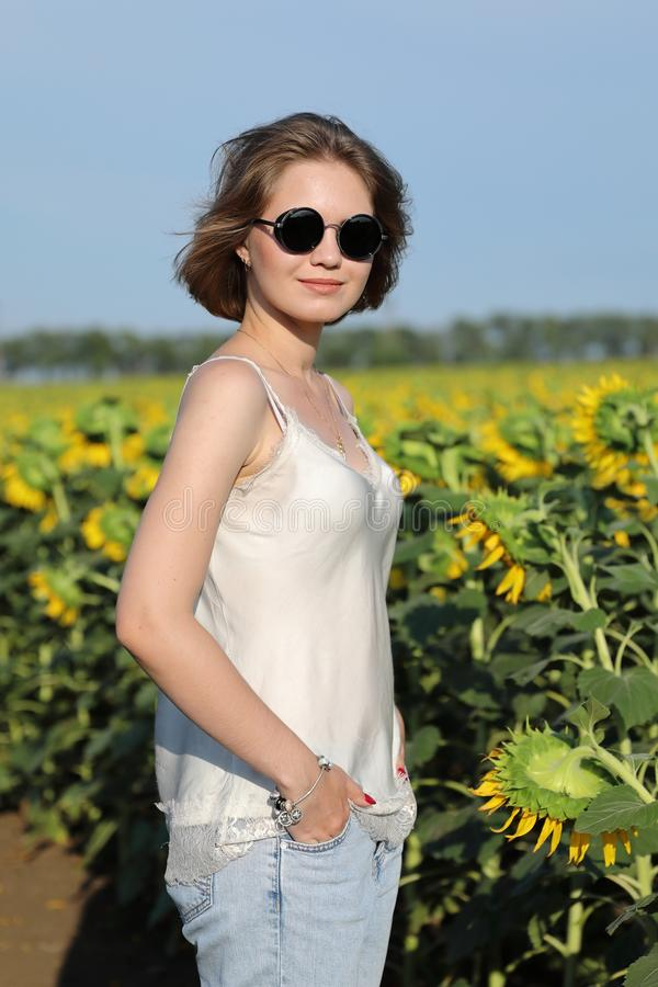 The girl in dark glasses walks on a sunset on the beautiful field of the blossoming sunflowers. royalty free stock images