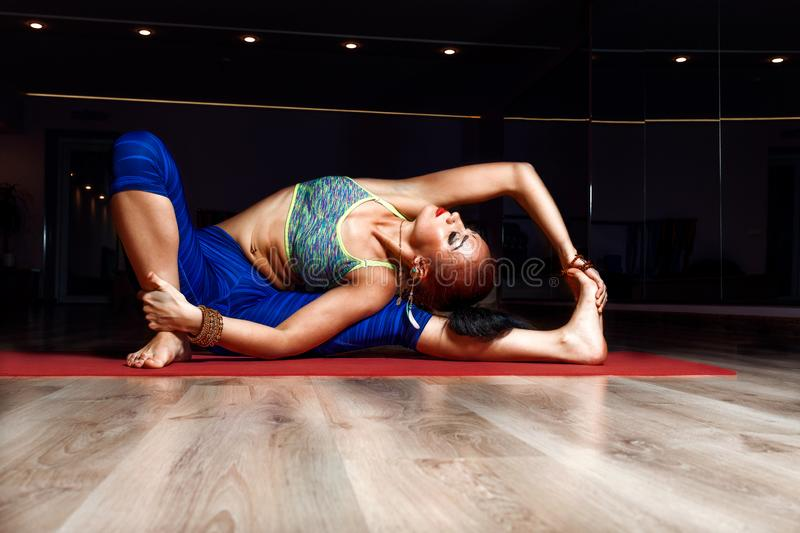A girl with dark hair does yoga in a darkened room on a red rug in a blue tight sports royalty free stock photos