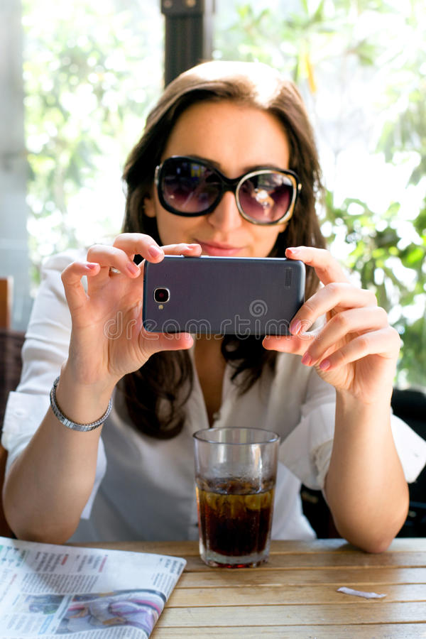 Girl with dark hair and glasses taking a selfie with a drink and newspaper royalty free stock image