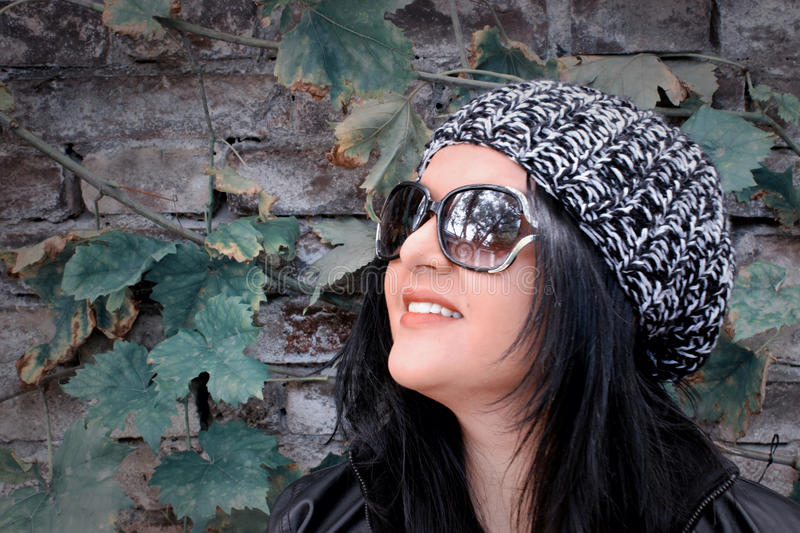 Girl With Dark Hair and Hat with Brick Wall Behind royalty free stock images