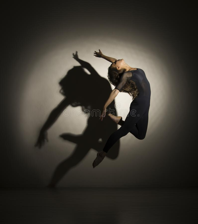 Girl in dark performs gymnastic jumping, on a white background there is a shadow from a shape. Studio photography stock photography