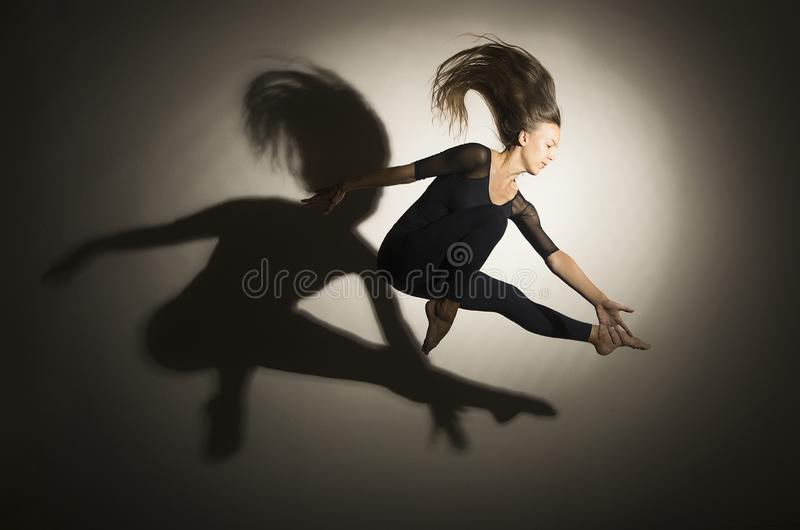 Girl in dark performs gymnastic jumping, on a white background there is a shadow from a shape. Studio photography stock photos