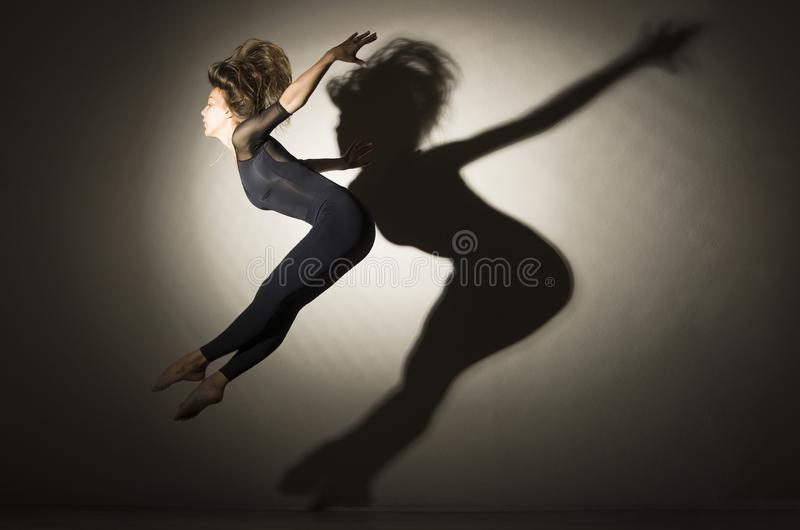 Girl in dark performs gymnastic jumping, on a white background there is a shadow from a shape. Studio photography royalty free stock image