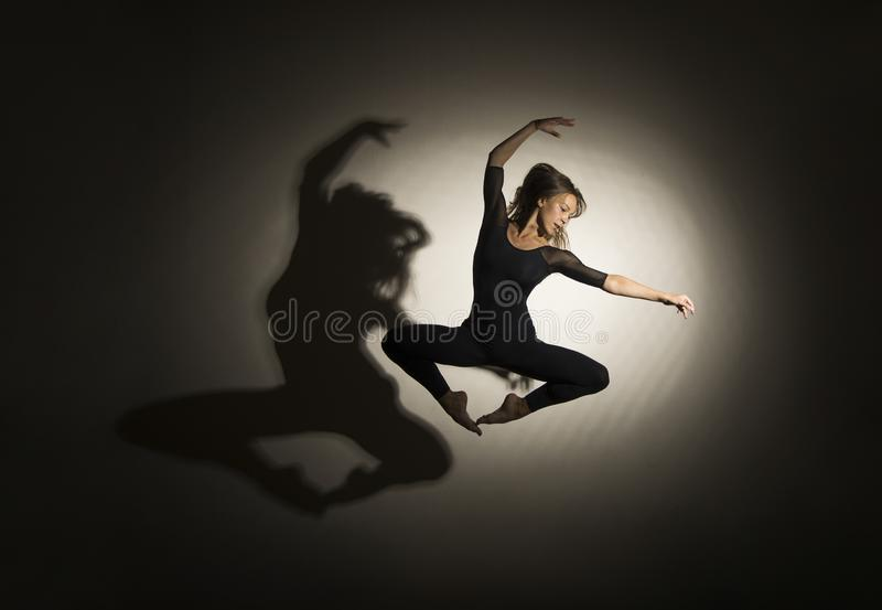 Girl in dark performs gymnastic jumping, on a white background there is a shadow from a shape. Studio photography royalty free stock photos