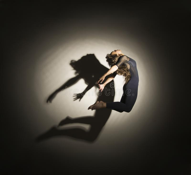 Girl in dark performs gymnastic jumping, on a white background there is a shadow from a shape. Studio photography stock photo