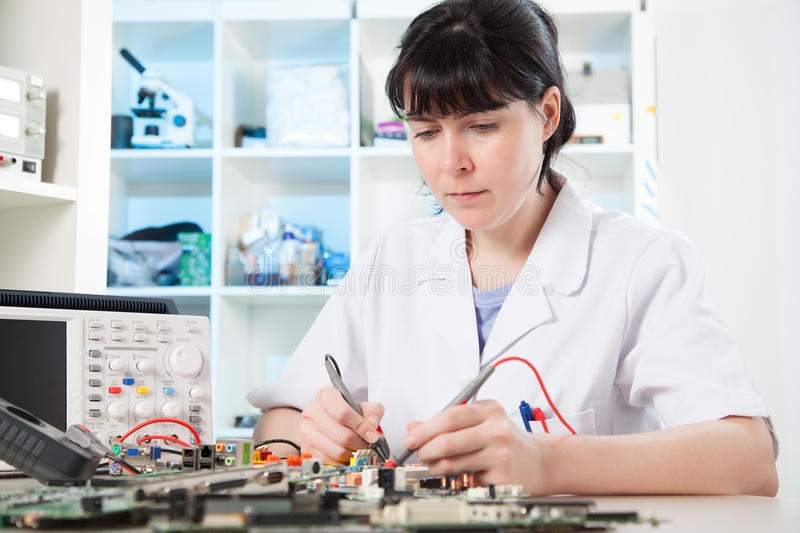 Debugging an electronic precision device. Girl debugging an electronic precision device royalty free stock images