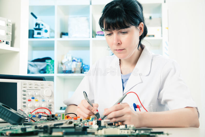 Girl with electronic device. Girl debugging an electronic precision device royalty free stock images