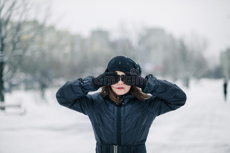 Girl decade closed eyes with handst background of winter landscape. child does not want to look. royalty free stock images