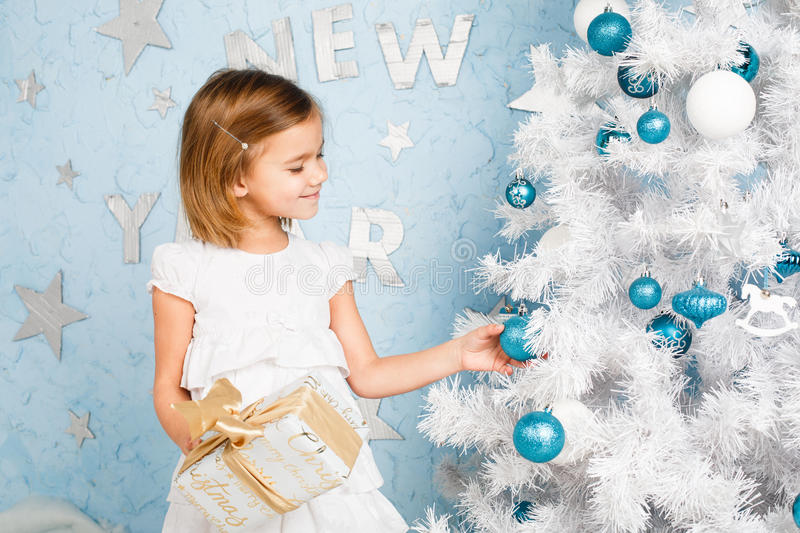 Girl decorates the Christmas tree balls and smiling royalty free stock images