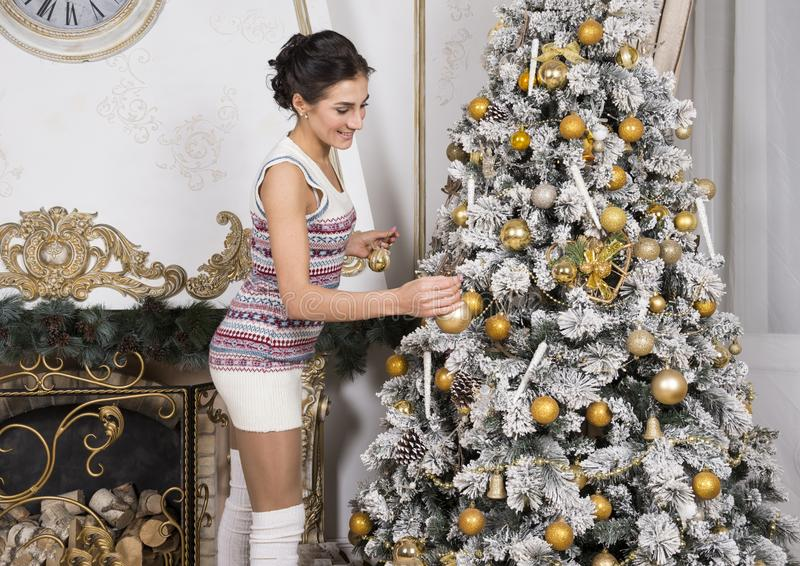 Girl decorates Christmas tree with Golden balls stock image