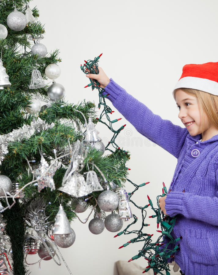 Girl Decorating Christmas Tree With Fairy Lights Royalty